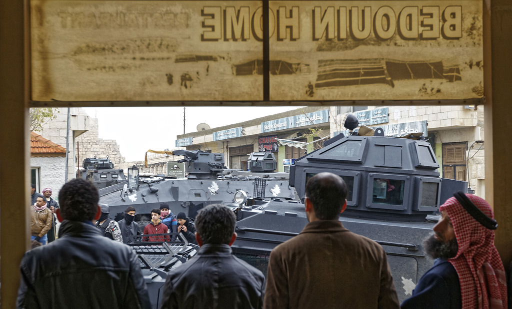 Onlookers gather under a shop awning as armored vehicles block the road in front of Karak Castle in the central town of Karak, about 14...