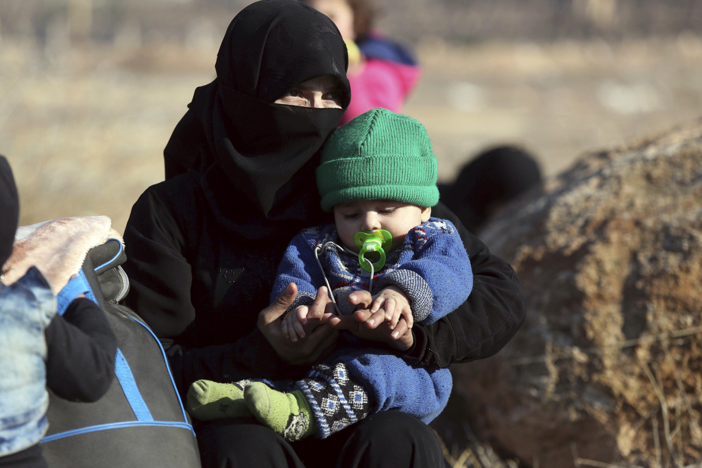 A Syrian woman holding a child who were  evacuated from the embattled Syrian city of Aleppo during the ceasefire arrive at a refugee ca...