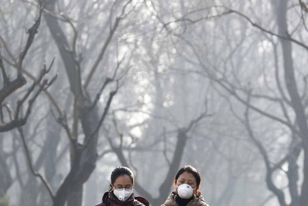 Chinese women wearing masks for protection against air pollution walk through Ritan Park shrouded by dense smog in Beijing, Monday, Dec...
