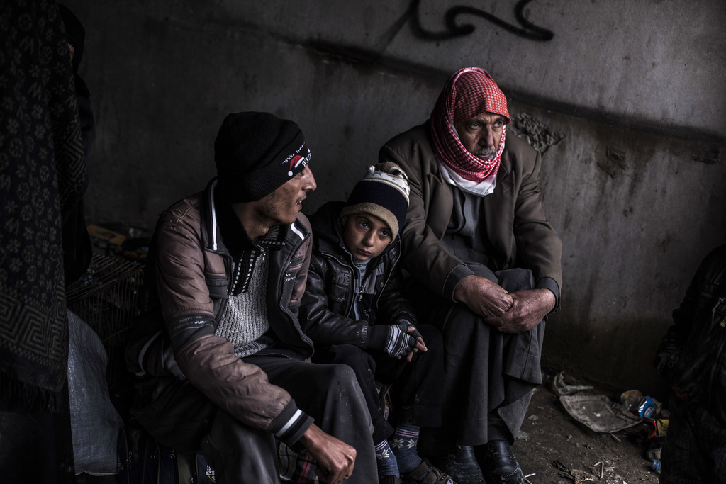 An Iraqi boy waits with his father and grandfather to be transferred to a camp near Mosul, Iraq, Monday, Dec. 19, 2016. Hundreds of Ira...