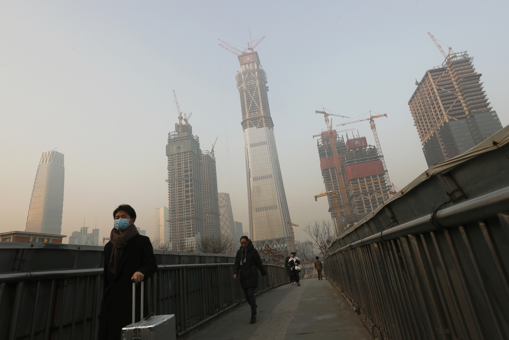 People, some wearing masks for protection against air pollution, walk on a pedestrian overhead bridge in Beijing as the capital of Chin...