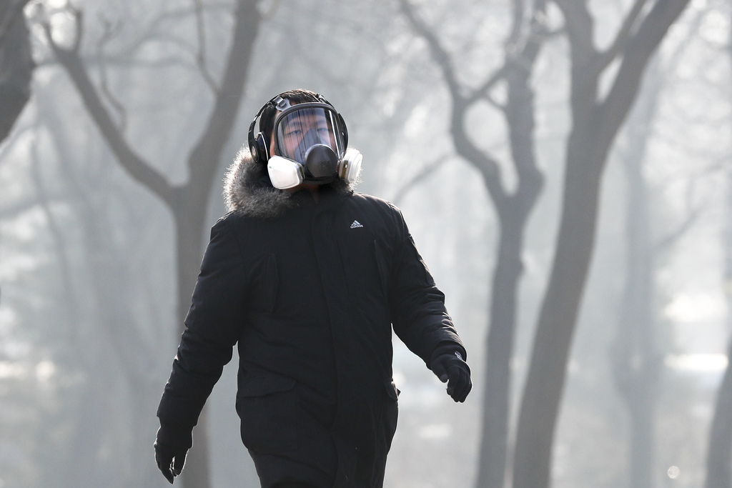 A man wearing a mask for protection against pollution exercise at Ritan Park during a heavily polluted day in Beijing, Monday, Dec. 19,...