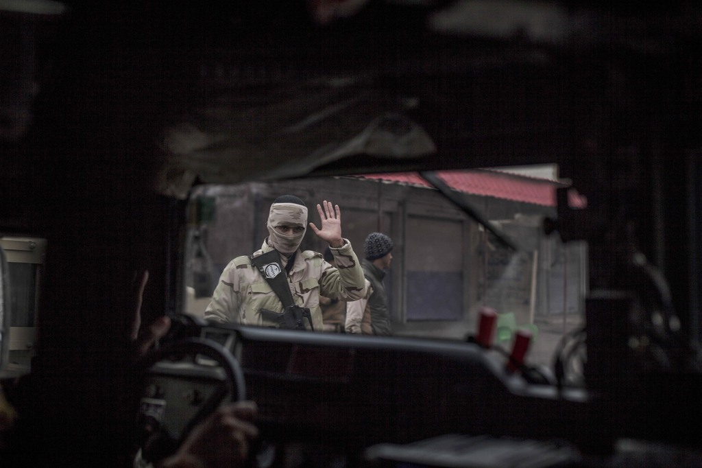 In this Sunday, Dec. 18, 2016 photo, an Iraqi soldier waves to comrades in a humvee heading to the front line in the al-Barid district ...