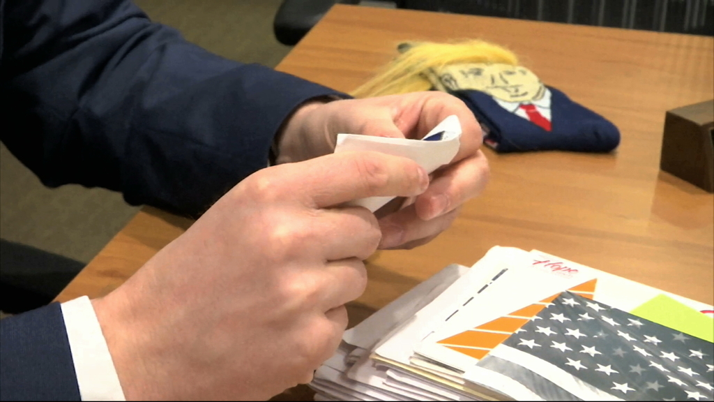 In this image from video, Electoral College elector Brian Fairbrother looks through mail he has received in Shelby Township, Mich., on ...