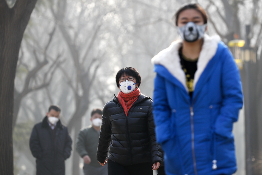 Chinese people wearing masks for protection against pollution walk at Ritan Park shrouded by heavy smog in Beijing, Monday, Dec. 19, 20...