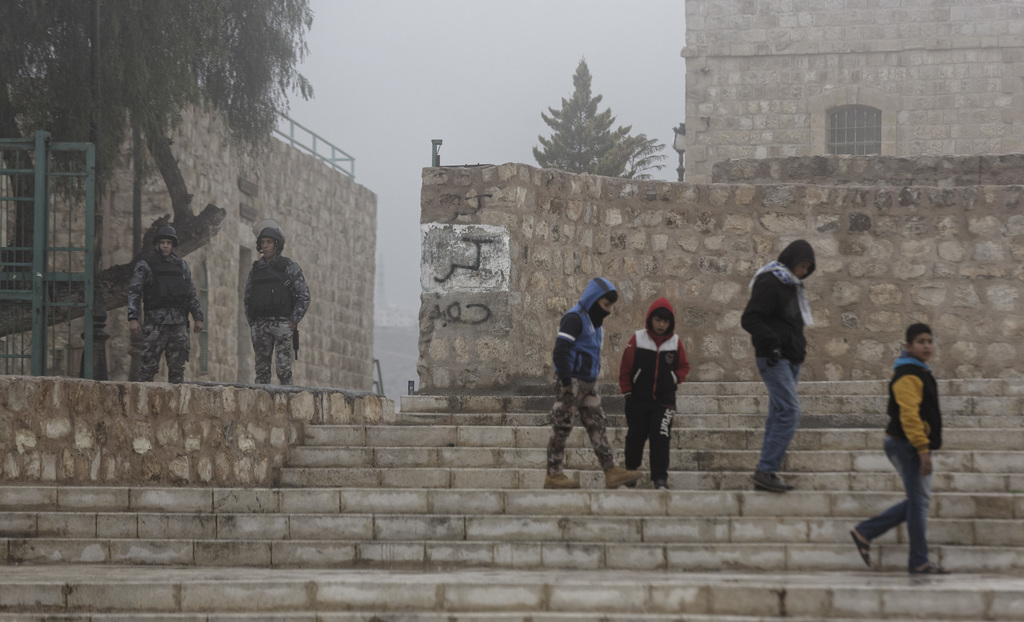 Jordanian security forces guard an entrance, left, as boys walk past in the morning mist in front of Karak Castle in the central town o...