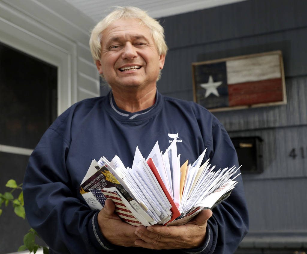 Rex Teter, a member of the Electoral College, holds two days of delivered mail at his home in Pasadena, Texas, Tuesday, Dec. 13, 2016. ...