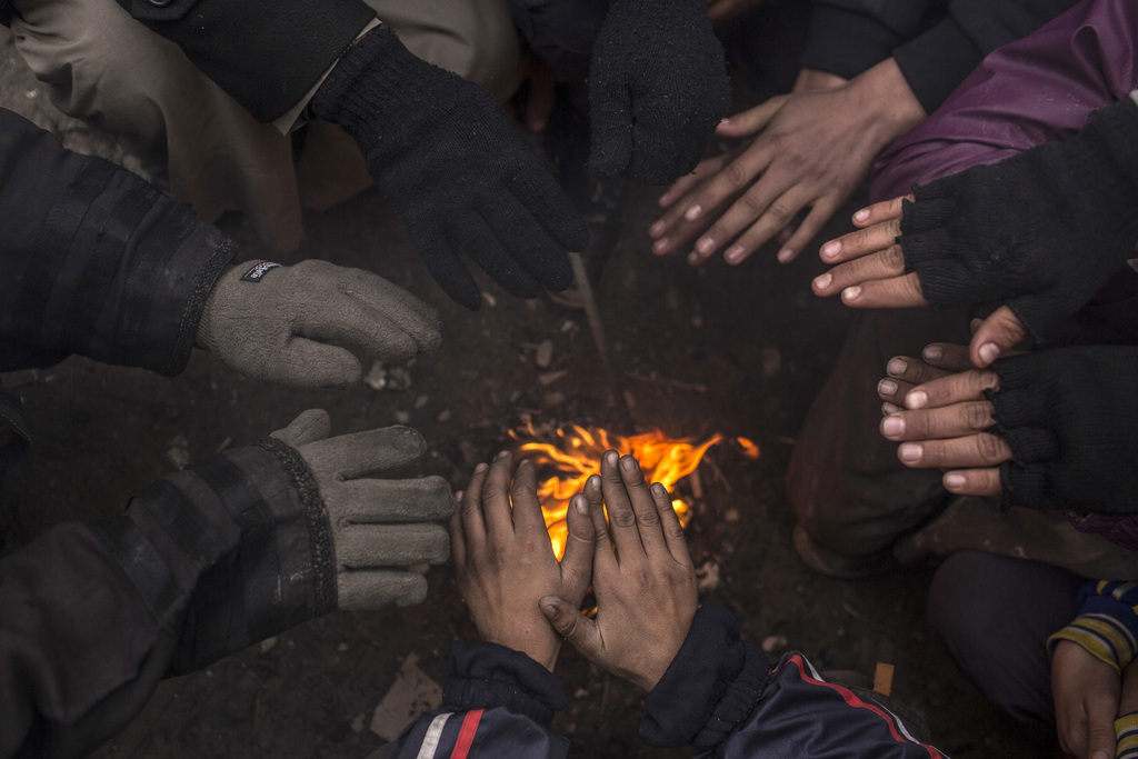 Displaced Iraqis warm themselves by a fire before being transferred to a camp near Mosul, Iraq, Monday, Dec. 19, 2016. Hundreds of Iraq...