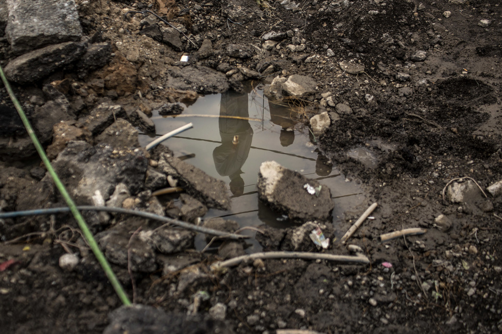 In this Sunday, Dec. 18, 2016 photo, Iraqi civilians are seen reflected in puddle made in the hole produced by a bomb in the al-Barid d...