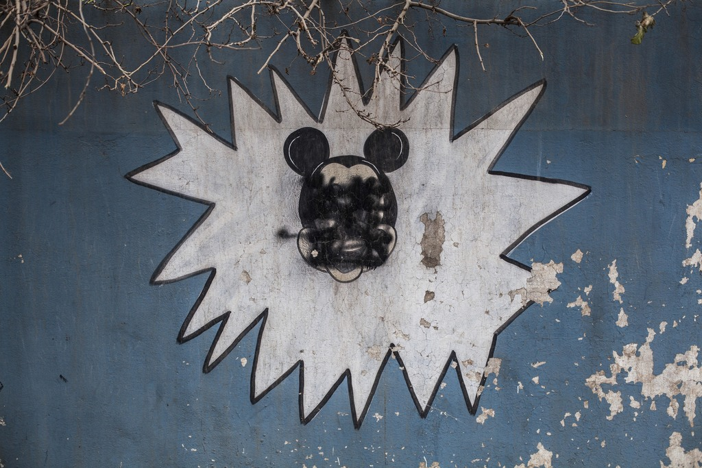 This Sunday, Dec. 18, 2016 photo shows a drawing of Mickey Mouse with its face painted over by Islamic States militants on the wall of ...