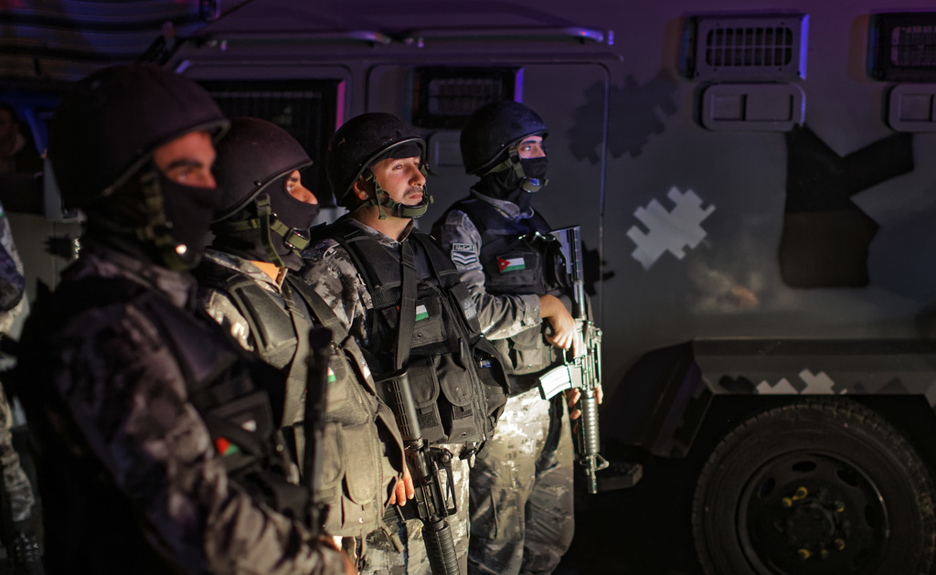 Jordanian security forces stand next to their armored vehicle at the scene next to Karak Castle, during an ongoing attack, in the centr...
