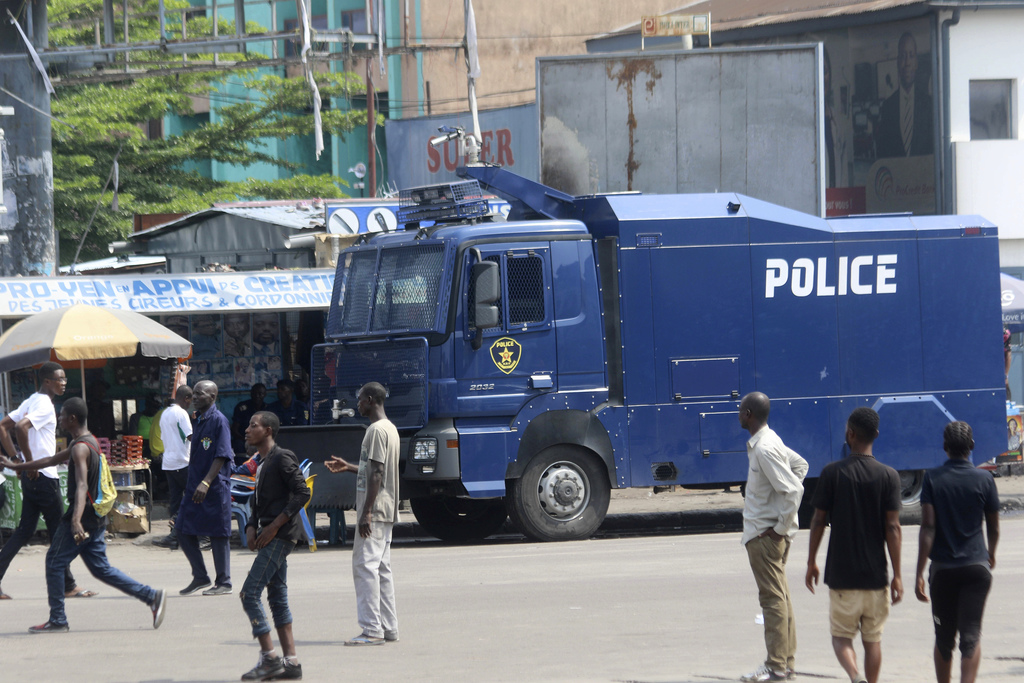 People walk past a police truck  in Kinshasa, Congo, Monday, Dec. 19, 2016. Military and police units are deployed across the capital o...