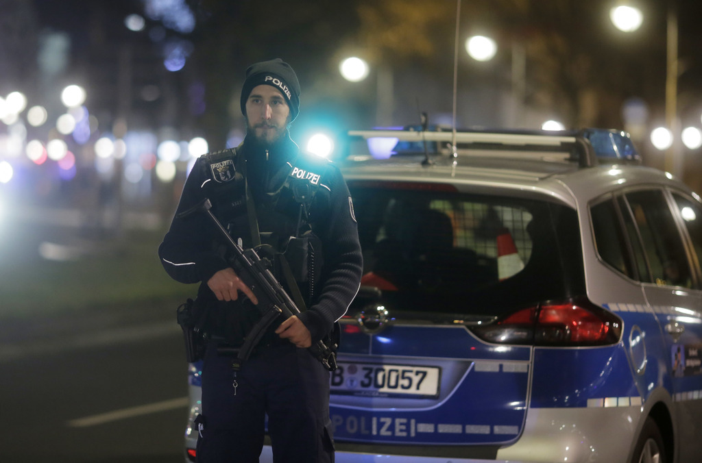 A police officer with a submachine gun stands guard after a truck ran into a crowded Christmas market in Berlin, Germany, Monday, Dec. ...