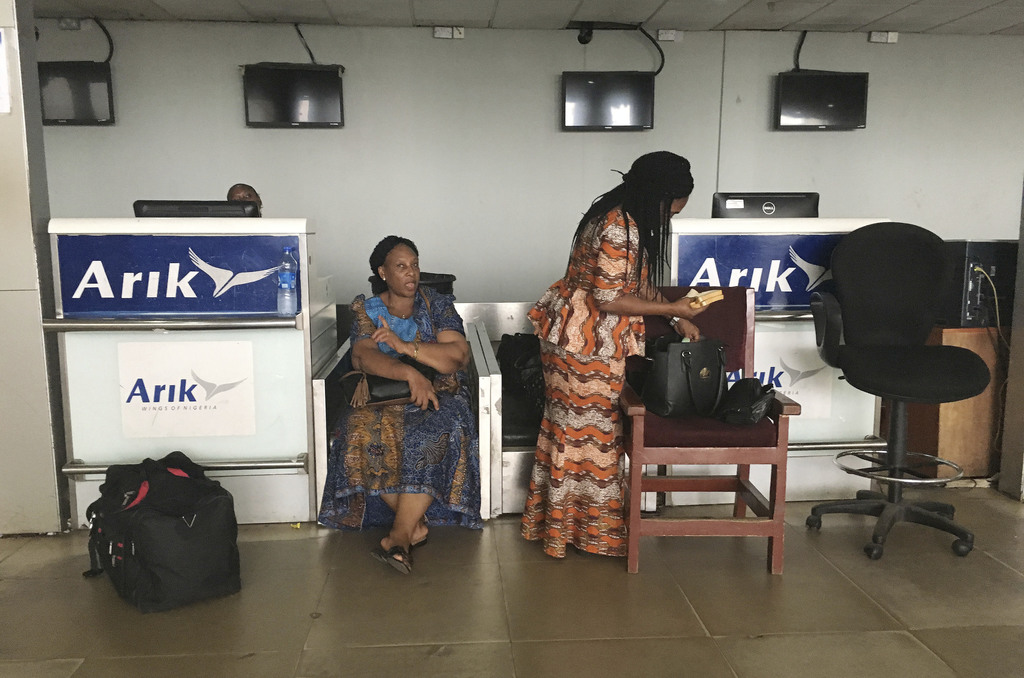 Stranded passengers stand at the closed Arik Air check-in counter following a protest over unpaid salaries by staff in Lagos, Nigeria, ...
