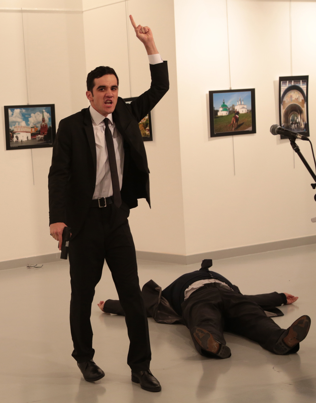 A man gestures after shooting Andrei Karlov, the Russian Ambassador to Turkey, on the floor, at a photo gallery in Ankara, Turkey, Mond...