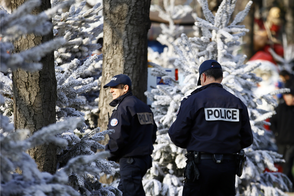 French Police officers patrol in the Champs Elysee Avenue Christmas market in Paris, Tuesday, Dec. 20, 2016 the day after a truck ran i...