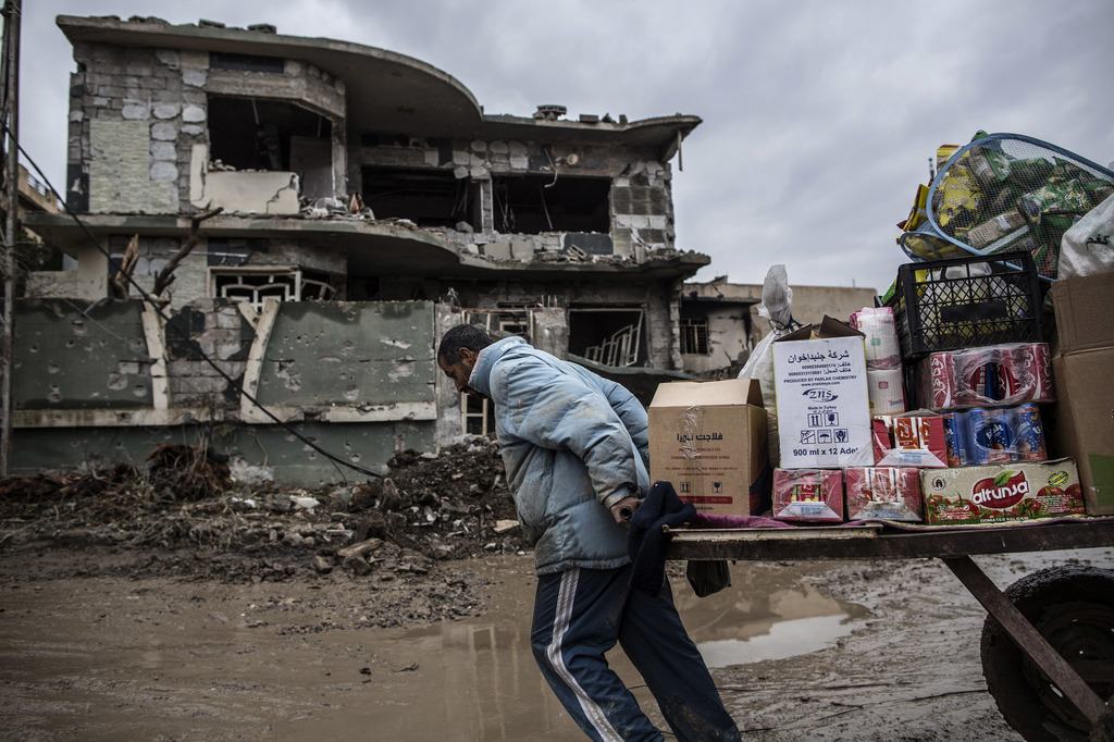 A street vendor pulls his cart in front of a house damaged by the fight in Mishraq district in Mosul, Iraq, Tuesday, Dec. 20, 2016. Adv...