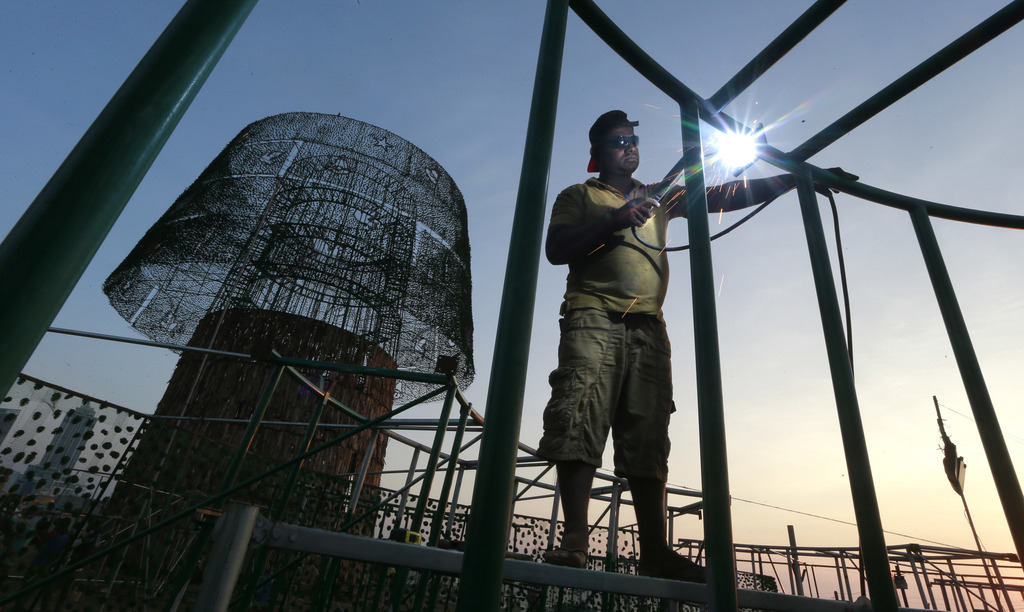 In this Thursday, Dec. 15, 2016 photo, a Sri Lankan port worker welds steel frames to assemble an enormous, artificial Christmas tree o...