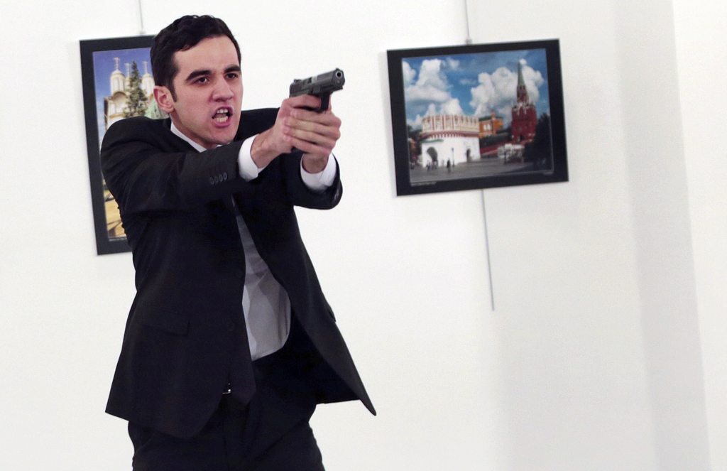 ADDS THE NAME OF THE GUNMAN - A man identified as Mevlut Mert Altintas holds up a gun after shooting Andrei Karlov, the Russian Ambassa...