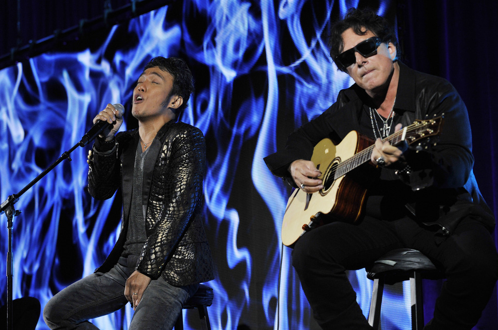 FILE - In this Aug. 6, 2013 file photo, Arnel Pineda, left, and Neal Schon of the rock band Journey perform onstage following a panel d...