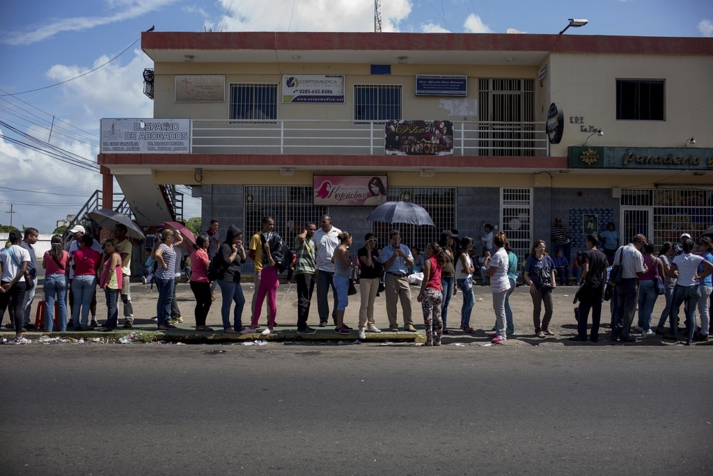 People line up to buy food in one of the two groceries stores that not was looted over the weekend, in Ciudad Bolivar, Venezuela, Monda...