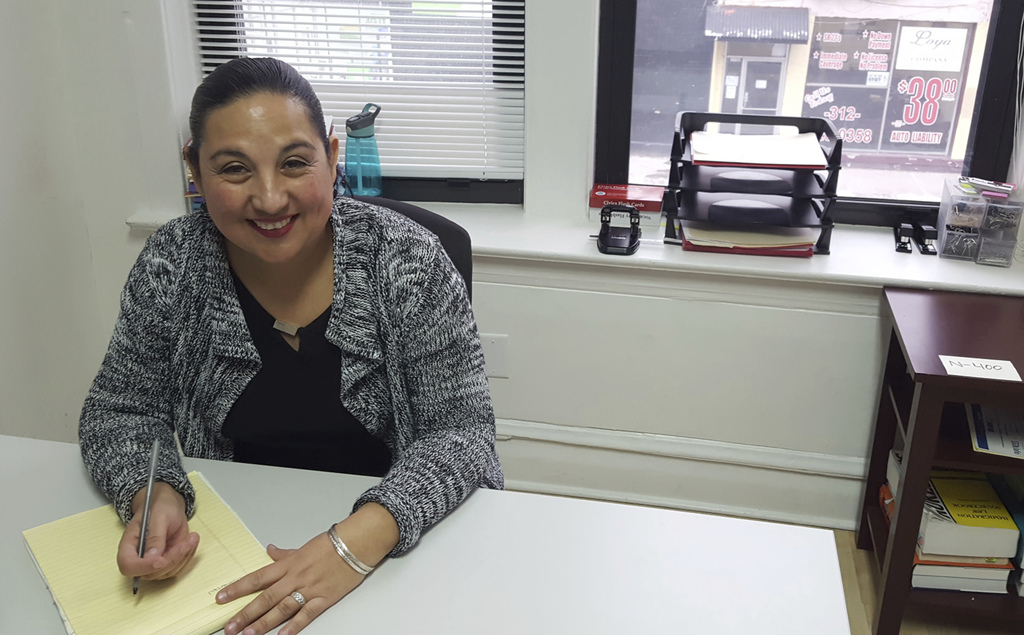 """In this Dec. 16, 2016 photo, Esperanza Villalobos, a """"community navigator,"""" works at her office at The Resurrection Project in Chicago...."""