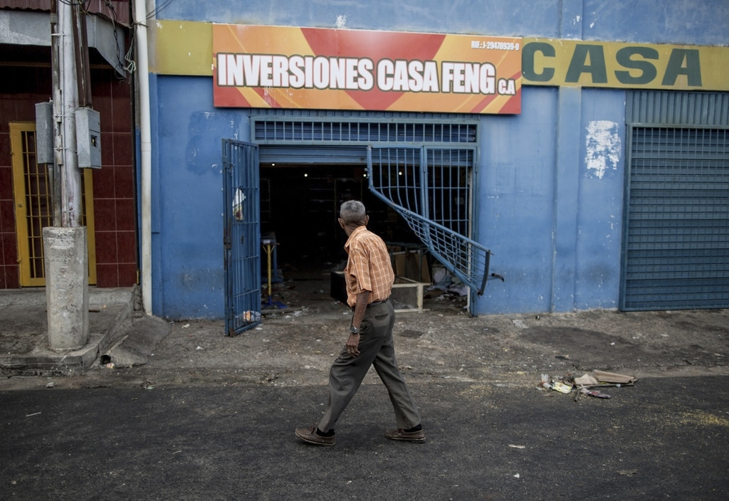 A man walks past a grocery store looted by demonstrators the night before in Ciudad Bolivar, Venezuela, Monday, Dec. 19, 2016. Last wee...