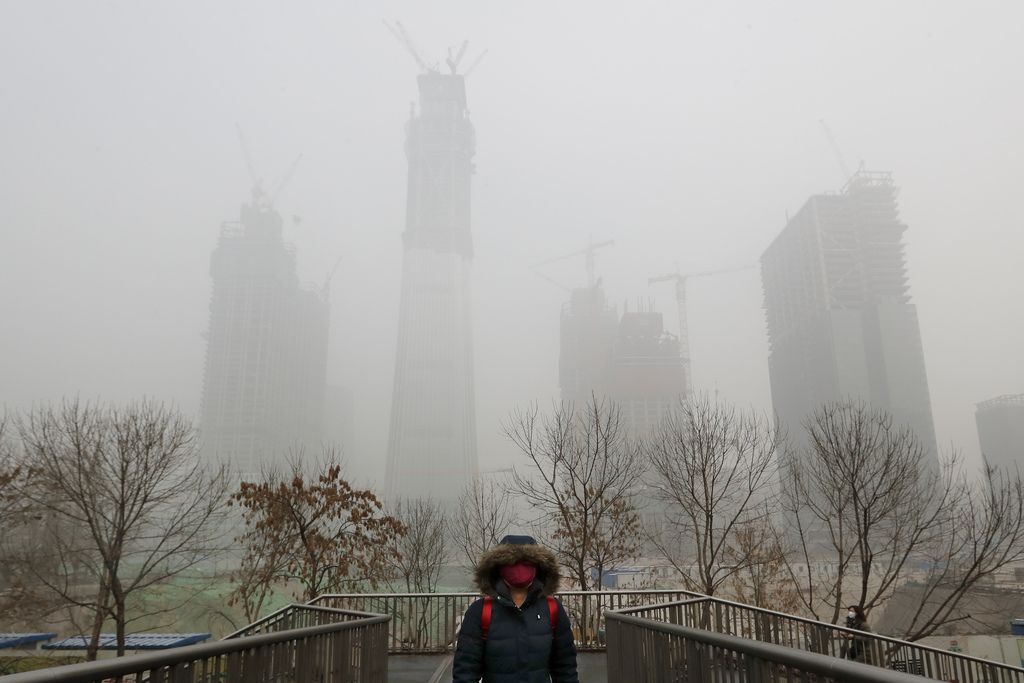 CORRECTS DAY OF WEEK - A woman wearing a mask for protection against air pollution walks on a pedestrian overhead bridge in Beijing as ...