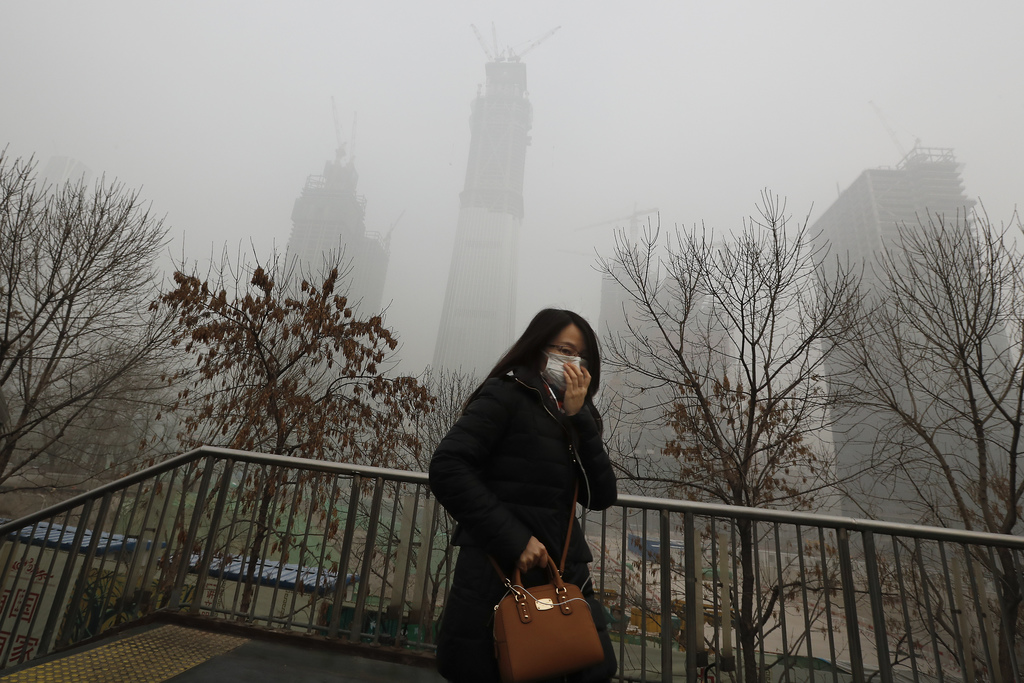 A woman holds her mask for protection against air pollution on a pedestrian overhead bridge in Beijing as the capital of China is shrou...