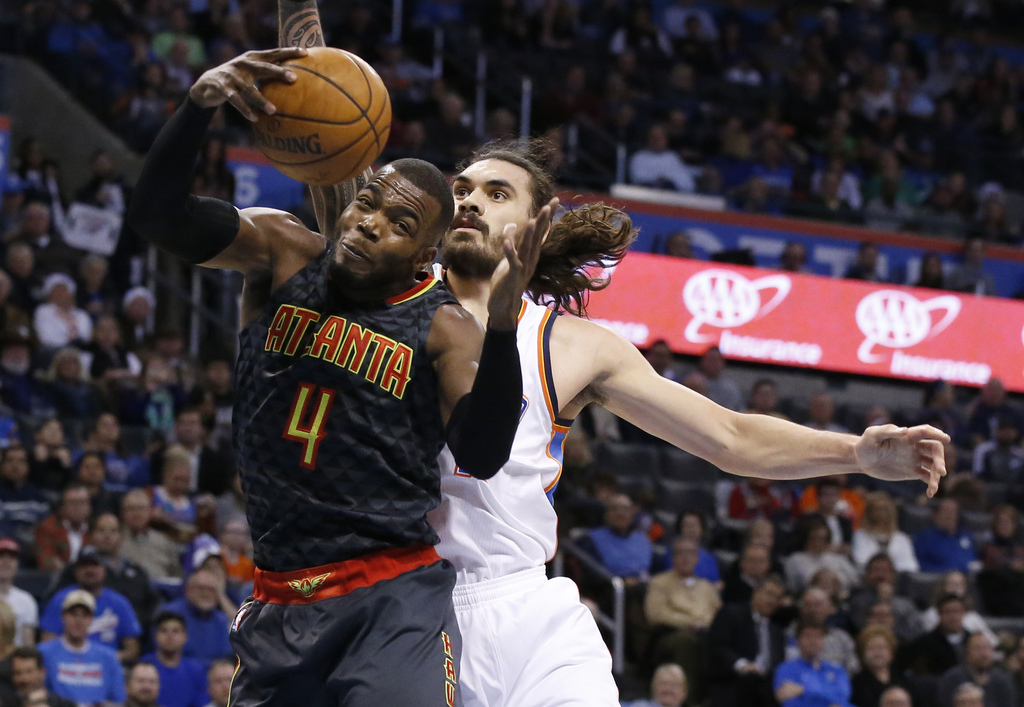 Atlanta Hawks forward Paul Millsap (4) grabs a rebound in front of Oklahoma City Thunder center Steven Adams, right, in the first half ...