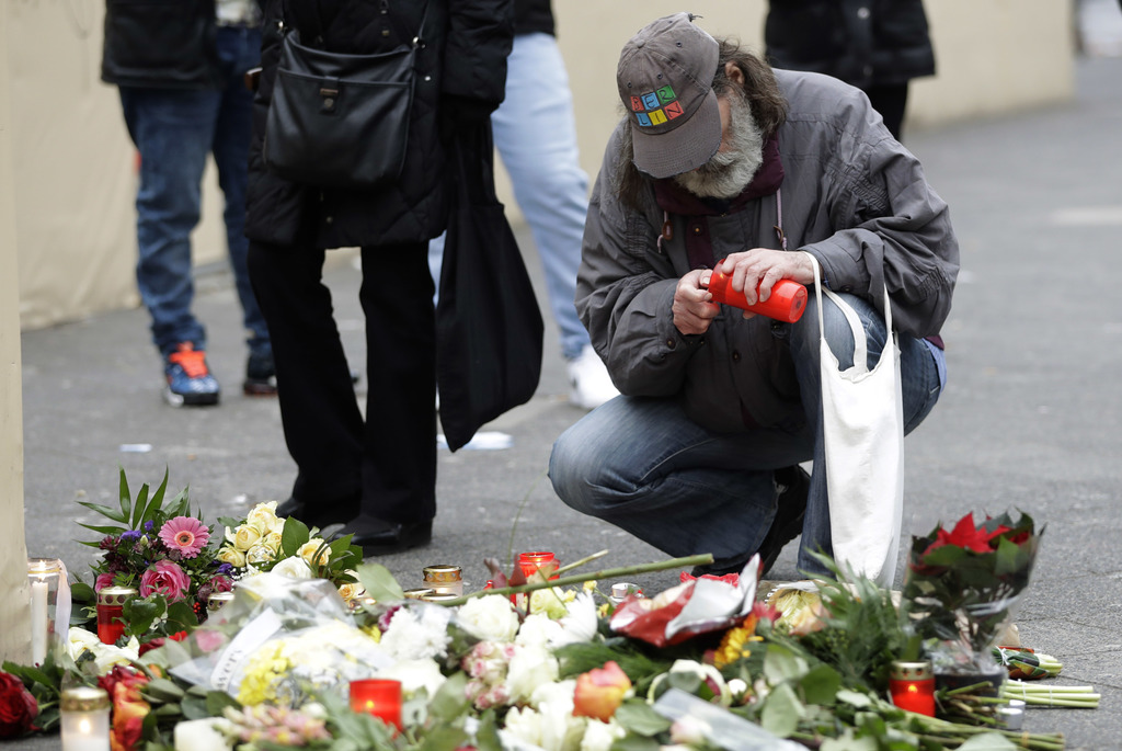 A man lights a candle in Berlin, Germany, Tuesday, Dec. 20, 2016, the day after a truck ran into a crowded Christmas market and killed ...