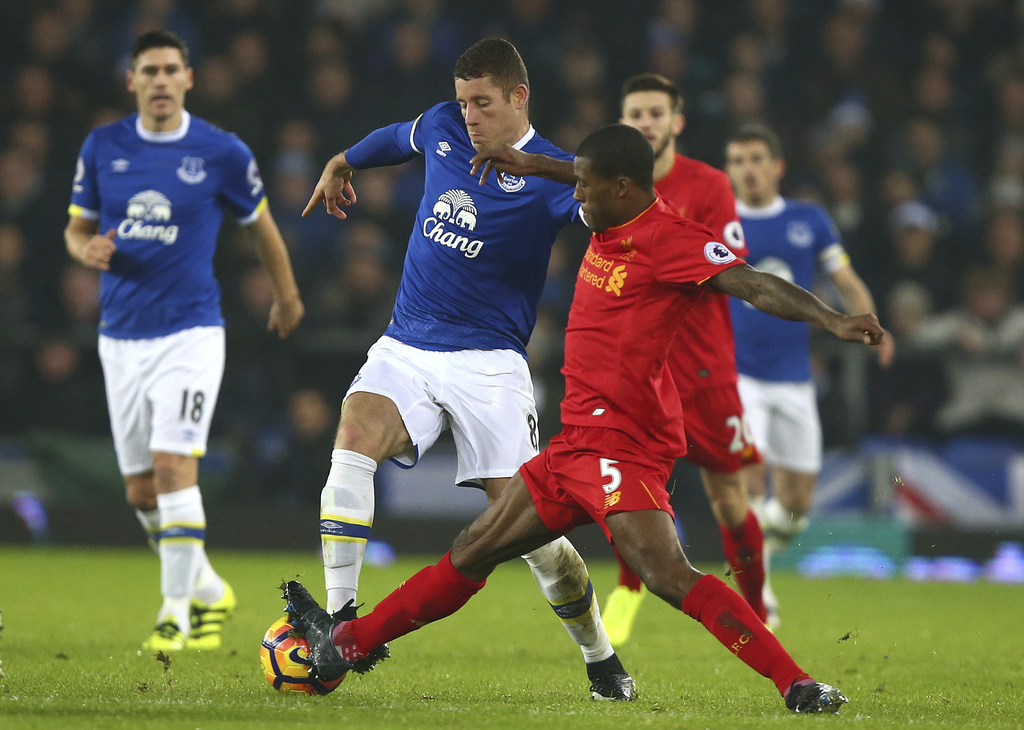 Everton's Ross Barkley, left, challenges for the ball with Liverpool's Georginio Wijnaldum during the English Premier League soccer mat...
