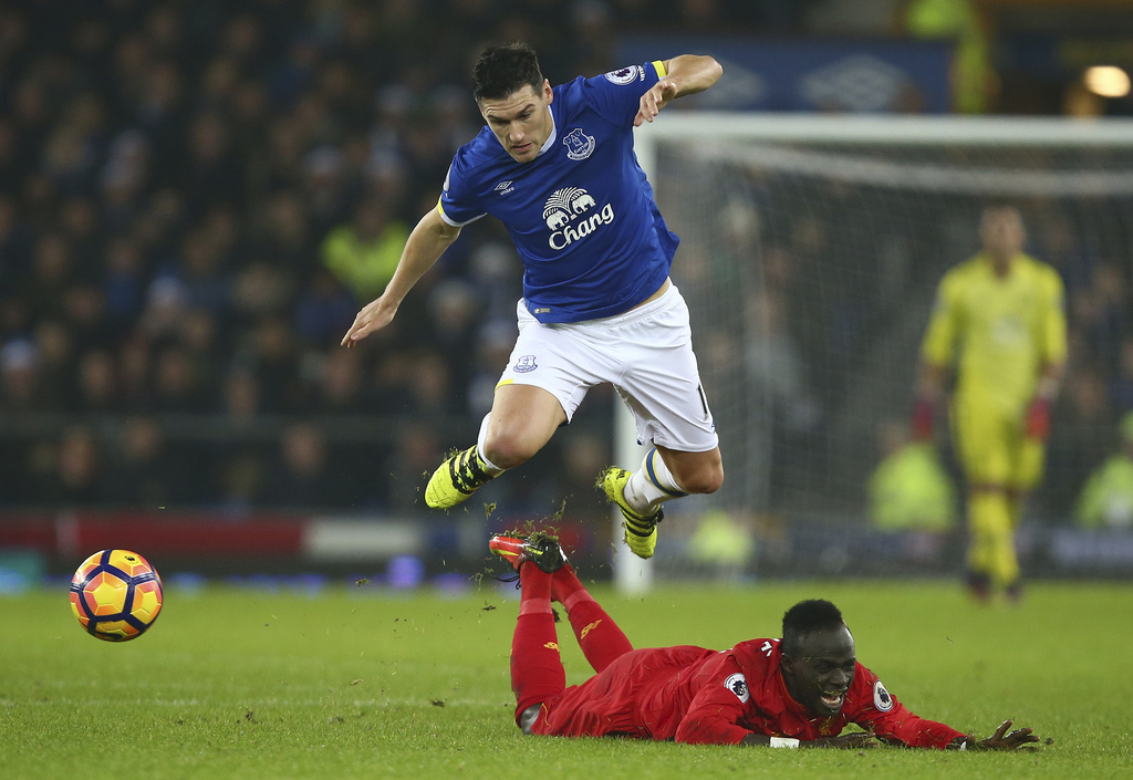 Everton's Gareth Barry leaps over Liverpool's Sadio Mane after they challenge for the ball during the English Premier League soccer mat...