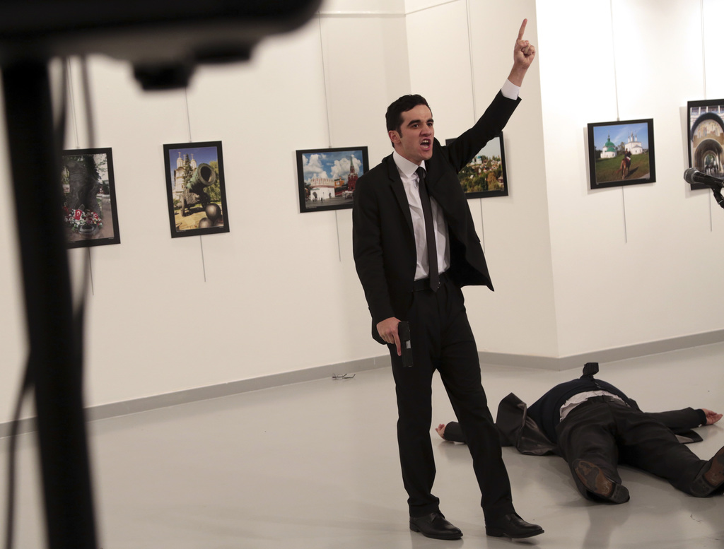 An unnamed gunman shouts after shooting the Russian Ambassador to Turkey, Andrei Karlov, at a photo gallery in Ankara, Turkey, Monday, ...