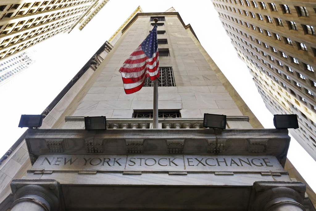FILE - In this Friday, Nov. 13, 2015, file photo, the American flag flies above the Wall Street entrance to the New York Stock Exchange...
