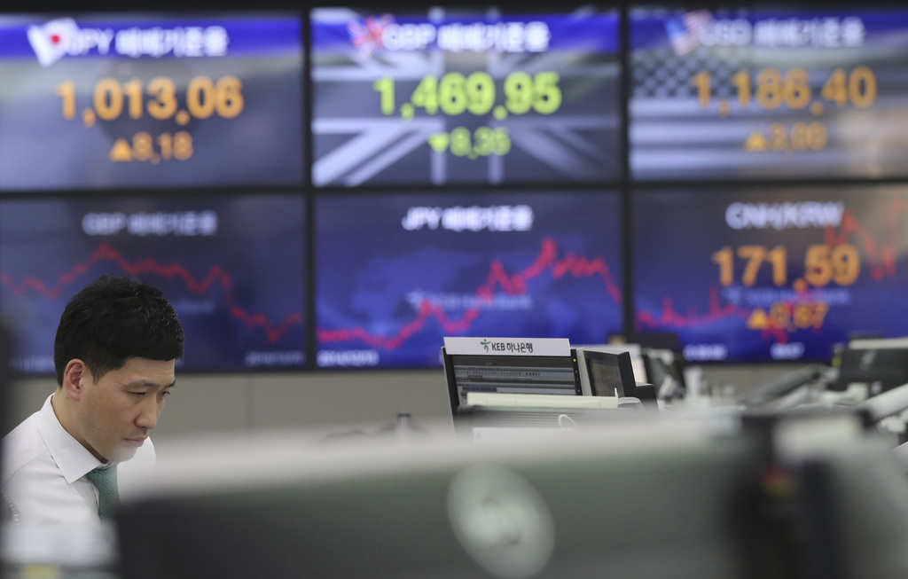 A currency trader watches monitors near the screens showing the foreign exchange rates at the foreign exchange dealing room in Seoul, S...