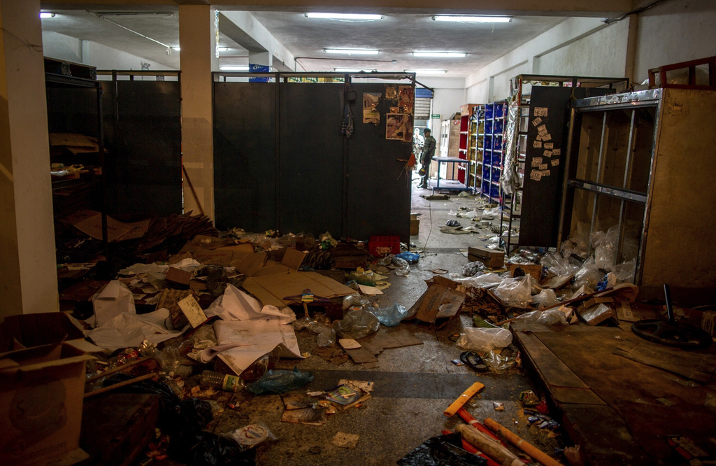Soldiers stand guard at the entrance of a store looted by demonstrators the night before, in Ciudad Bolivar, Venezuela, Monday, Dec. 19...