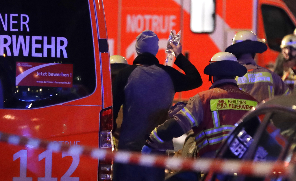 Firefighters attend an injured person after a truck ran into crowded Christmas market in Berlin, Germany, Monday, Dec. 19, 2016. Police...