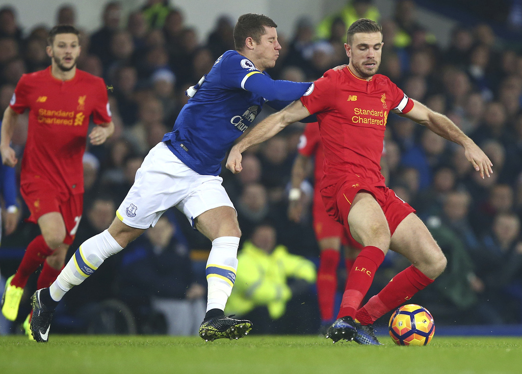 Liverpool's Jordan Henderson, right, vies for the ball with Everton's Ross Barkley during the English Premier League soccer match betwe...