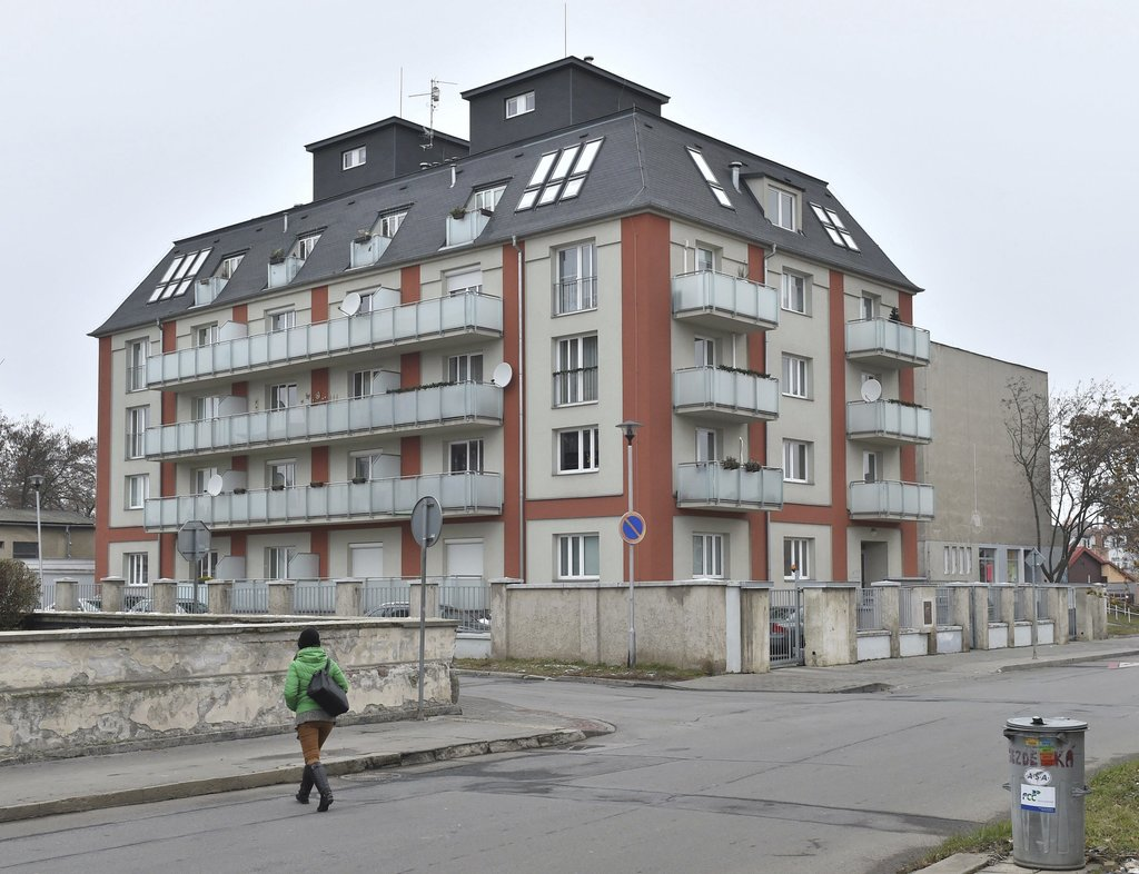 A woman crosses a street in front of the house where Czech tennis player Petra Kvitova has been attatcked and injured in her flat in Pr...