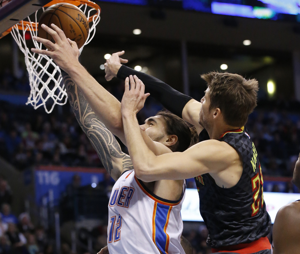 Oklahoma City Thunder center Steven Adams, left, is fouled by Atlanta Hawks guard Kyle Korver, right, as he reaches for the ball in the