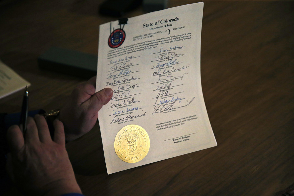 A Colorado elector holds a signed vote certificate during the electoral vote at the Capitol in Denver, Monday, Dec. 19, 2016. Colorado'...