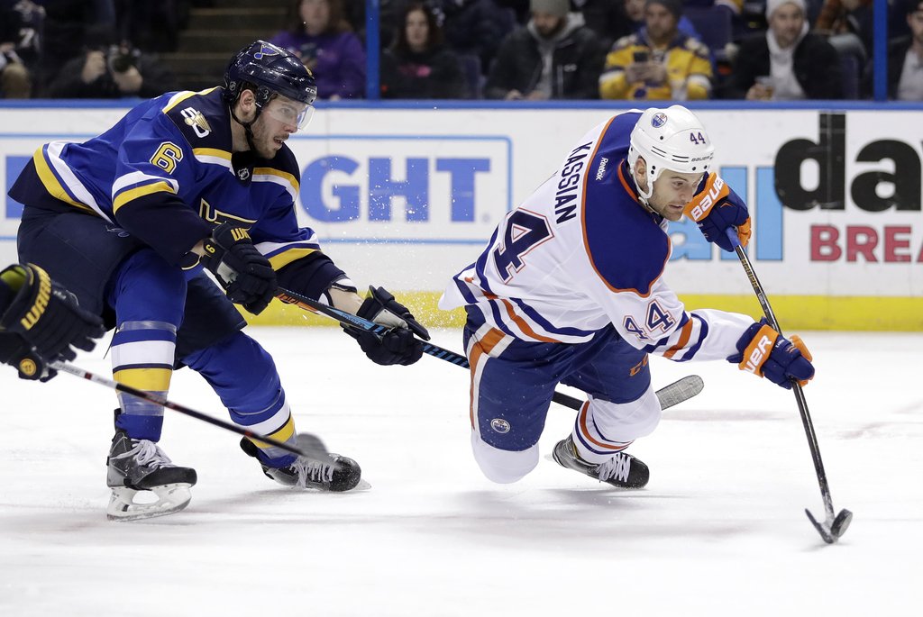 Edmonton Oilers' Zack Kassian, right, tries to get off a shot as St. Louis Blues' Joel Edmundson defends during the third period of an ...