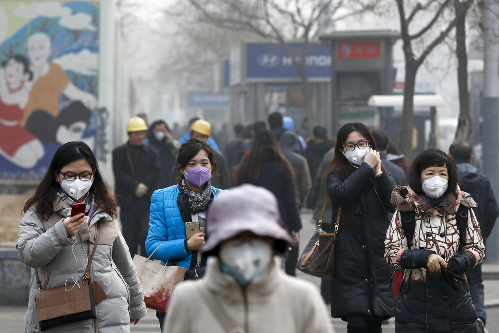 CORRECTS DAY OF WEEK - Women wearing protection masks walk on a street in Beijing as the capital of China is shrouded by heavy smog on ...