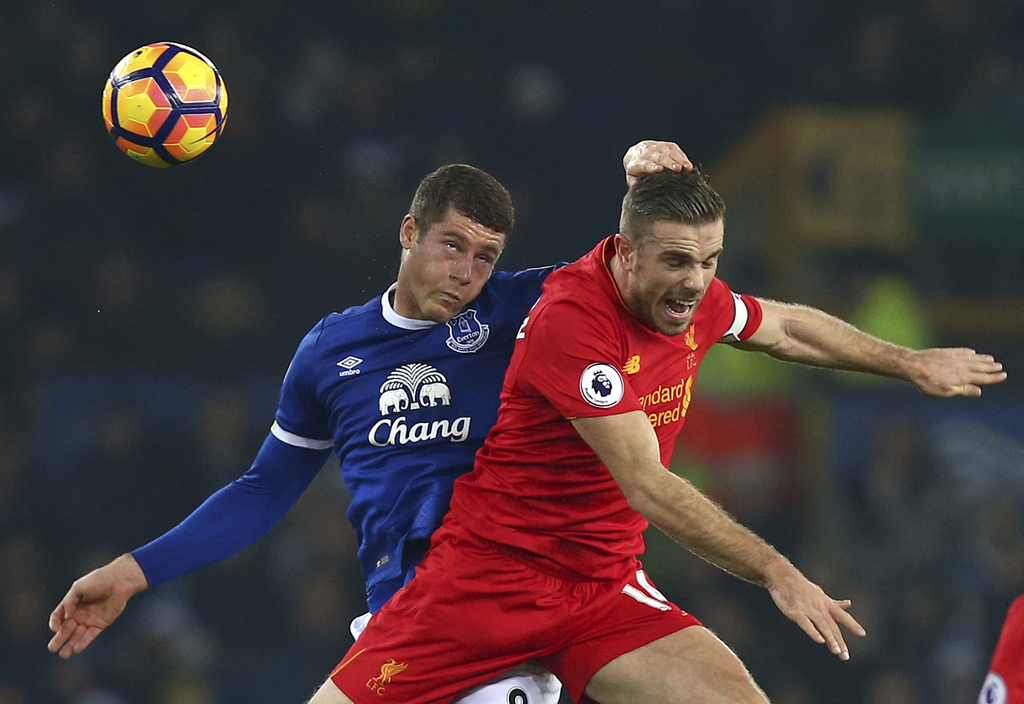 Everton's Ross Barkley, left, challenges for the ball with Liverpool's Jordan Henderson during the English Premier League soccer match ...