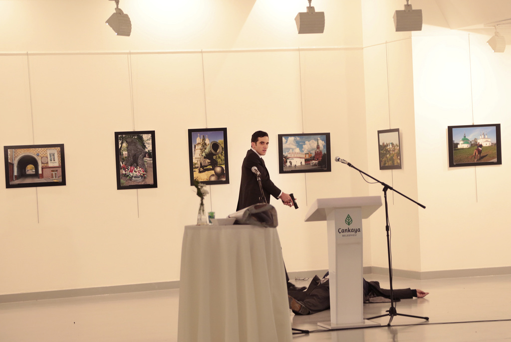 An unnamed gunman gestures after shooting the Russian Ambassador to Turkey, Andrei Karlov, at a photo gallery in Ankara, Turkey, Monday...