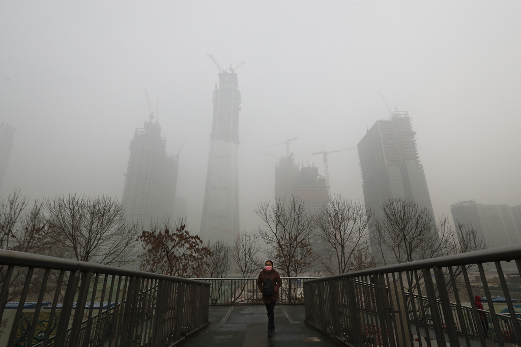 A woman wearing a mask for protection against air pollution walks on a pedestrian overhead bridge in Beijing as the capital of China is...