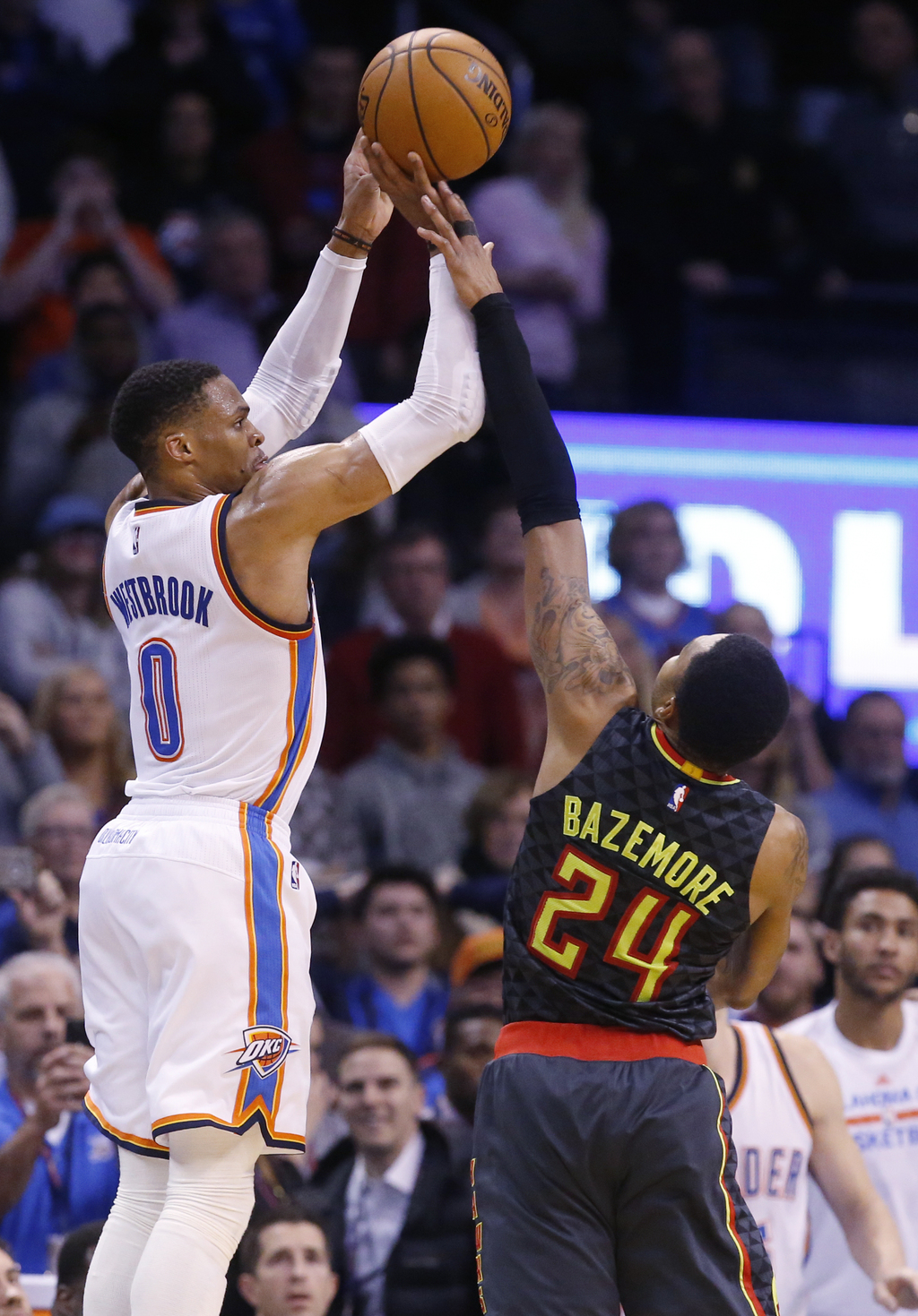 Oklahoma City Thunder guard Russell Westbrook (0) attempts a 3-point basket in front of Atlanta Hawks forward Kent Bazemore (24) in the...