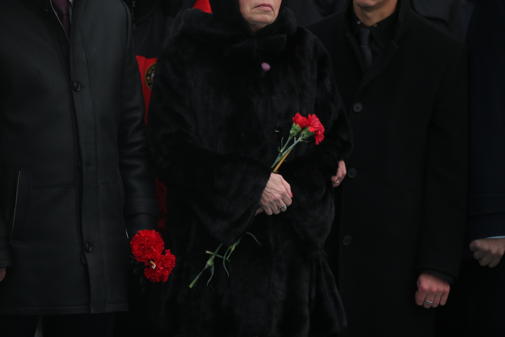 Marina, the wife of Russian Ambassador to Turkey Andrei Karlov who was assassinated Monday, holds flowers during a ceremony at the airp