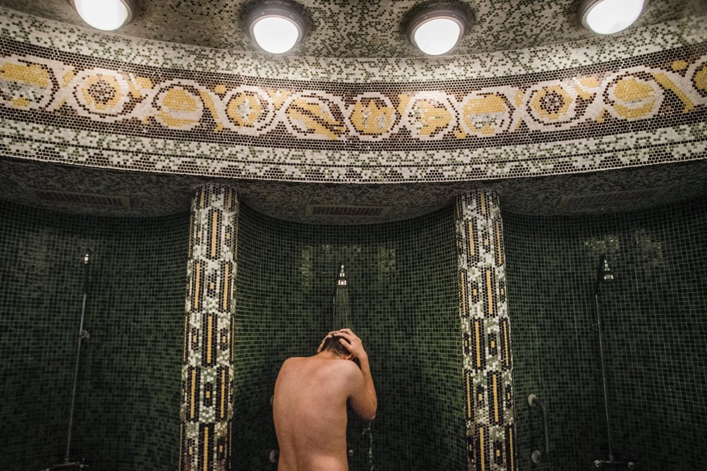 FILE - In this March 21, 2016 file photo a visitor takes a shower in Szechenyi Thermal Bath and Swimming Pool in Budapest, Hungary. The...